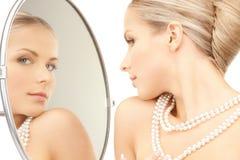 Schöne Frau mit Perlenkornen und -spiegel lizenzfreie stockbilder