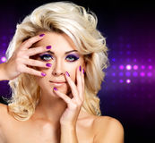 Schöne Frau mit purpurroter Maniküre der Schönheit und Make-up der Augen. Stockfoto