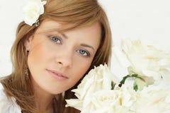 Schöne Frau mit rosafarbenen Blumen Stockfotografie