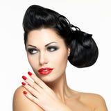 Schöne Frau mit roten Nägeln und den Lippen Stockbild
