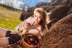 Schöne Frau mit vielen Apfel im Korb Stockbild