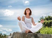 Schöne Frau 50s, die auf einem Stein in Yogalotussitz sitzt Stockfoto