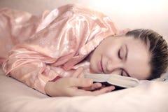 Schöne Frau schläft mit Buch im Bett Lizenzfreie Stockbilder