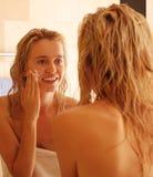 Schöne Frau setzt eine Gesichtssahne nach einer Dusche stockbild