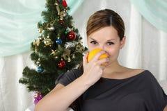 Schöne Frau sitzt nahe einem Weihnachtenc$pelzbaum Stockbilder