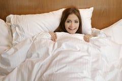 Schöne Frau steht auf weißem Bett still Lizenzfreies Stockbild