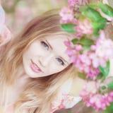 Schöne Frau und blühender Baum Stockfotografie