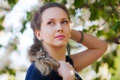 Schöne Frau unter blühenden Bäumen stockfoto