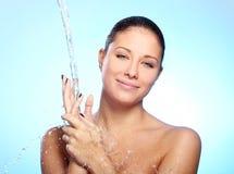 Schöne Frau unter Spritzen des Wassers Stockfotografie