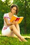 Schöne Frau untergetaucht in einem romantischen Buch Lizenzfreie Stockfotos