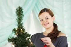 Schöne Frau verzieren einen Weihnachtenc$pelzbaum Lizenzfreies Stockfoto