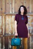 Schöne Frau von mittlerem Alter in einem Burgunder-Kleid und in einer grünen Handtasche stockfoto