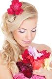 Schöne Frau, welche die Blumen betrachtet Lizenzfreie Stockfotos