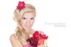 Schöne Frau, welche die Blumen betrachtet Lizenzfreies Stockbild