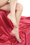 Schöne Frauenfüße über Weiß mit rotem Gewebe stockbild