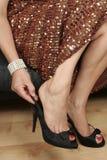 Schöne Frauenfahrwerkbeine mit dem Kleid, das auf Schuhe sich setzt Stockfoto
