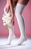 Schöne Frauenfahrwerkbeine mit weißer Orchidee Lizenzfreies Stockfoto