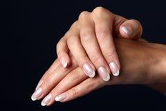 Schöne Frauenhand mit französischer Maniküre Stockfotografie