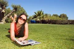Schöne Frauenlesezeitschrift im Park Lizenzfreies Stockfoto