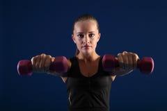 Schöne Frauenstärkenübung mit Gewichten Lizenzfreie Stockfotografie
