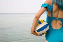 Schöne Fraurückseite in Badeanzug, farbiges Haar mit volleyb lizenzfreie stockfotografie