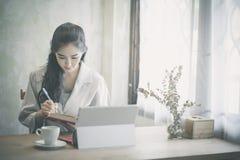 Schöne Freiberufler-Frau, die online an ihrem Haus arbeitet lizenzfreie stockfotografie