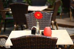 Schöne Freilichtsommer-Restauranttabellen mit roter Blume im Vase Lizenzfreies Stockfoto