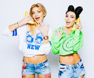 Schöne Freundinnen Blondine und Brunette, die Spaß und das Lächeln haben Kurz gesagt, Jeans T-Shirt und Hoodie tragen Spielen Lizenzfreies Stockbild