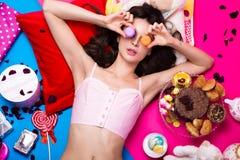 Schöne frische Mädchenpuppe, die auf den hellen Hintergründen umgeben durch Bonbons, Kosmetik und Geschenke liegt Modeschönheitsa Stockfotos