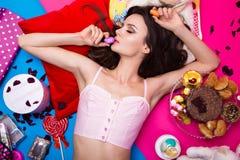 Schöne frische Mädchenpuppe, die auf den hellen Hintergründen umgeben durch Bonbons, Kosmetik und Geschenke liegt Modeschönheitsa Stockbild