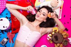 Schöne frische Mädchenpuppe mit den Seifenblasen, die auf den hellen Hintergründen umgeben durch Bonbons, Kosmetik und Geschenke  Lizenzfreie Stockfotos