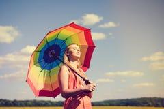 Schöne frohe junge Frau mit Regenbogen Stockfoto