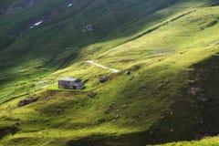 Schöne Gebirgslandschaft Grüne Alpenwiesen, Gebirgshaus Kühe lassen auf den Gebieten weiden Roter Plastikmarkierungsfahnenstift,  lizenzfreie stockfotografie