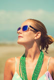Schöne gebräunte blonde Frau auf dem Strand ein Sonnenbad nehmend Stockfoto