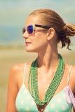 Schöne gebräunte blonde Frau auf dem Strand ein Sonnenbad nehmend Lizenzfreie Stockfotografie