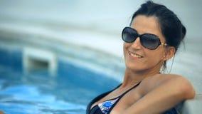 Schöne gebräunte Frau, die im Bikini und in der Sonnenbrille im Swimmingpool sich entspannt stock video