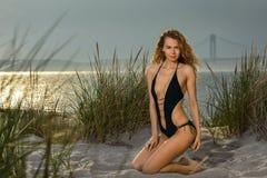 Schöne gebräunte Frau mit dem blonden Haar im sexy schwarzen Badeanzug, der auf dem Strand aufwirft Stockbild