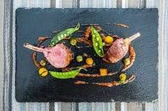 Schöne gebratene Lamm-Rippen mit grüner Bohne und Kraut Sauce auf Querstation lizenzfreie stockfotografie