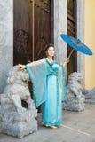 Schöne Geisha mit einem blauen Regenschirm Stockfotografie