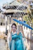 Schöne Geisha mit einem blauen Regenschirm Lizenzfreies Stockfoto