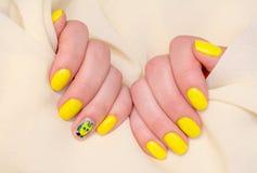 Schöne gelbe Nagelmaniküre Helle Maniküre im Licht auf einem weißen Hintergrund stockfotos