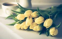 Schöne gelbe Tulpen auf der weißen hölzernen Hintergrund-Tasse Kaffee-Frühstücks-Morgen-Feiertags-Geburtstags-Zusammensetzung get Lizenzfreies Stockfoto