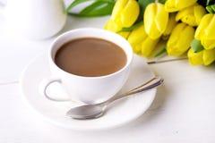 Schöne gelbe Tulpen auf weißem hölzernem Hintergrund-Tasse Kaffee-Frühstücks-Morgen-Feiertags-Geburtstags-Zusammensetzungs-Abschl Stockbilder