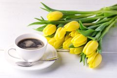 Schöne gelbe Tulpen auf weißer hölzerner Hintergrund-Tasse Kaffee-Frühstücks-Morgen-Feiertags-Geburtstags-Zusammensetzung Lizenzfreie Stockbilder