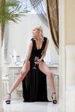 Schöne gelockte blonde Aufstellung im langen schwarzen Kleid Lizenzfreies Stockfoto
