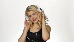 Schöne gelockte blonde tragende Kopfhörer, die Musik hören weiß Langsame Bewegung stock footage