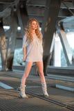 Schöne gelockte junge Frau, die auf industriellem Brücke locati steht Stockfotos