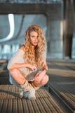 Schöne gelockte junge Frau, die auf industriellem Brücke locatio sitzt Lizenzfreies Stockbild