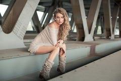 Schöne gelockte junge Frau, die auf industriellem Brücke locatio sitzt Lizenzfreie Stockbilder