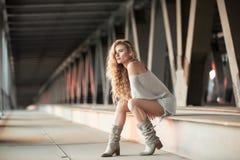 Schöne gelockte junge Frau, die auf industriellem Brücke locatio sitzt Stockfoto